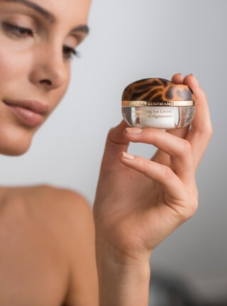 Model holding eye cream